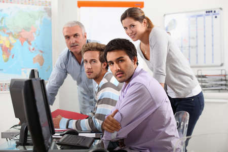 Group of casually dressed people working round a computer photo