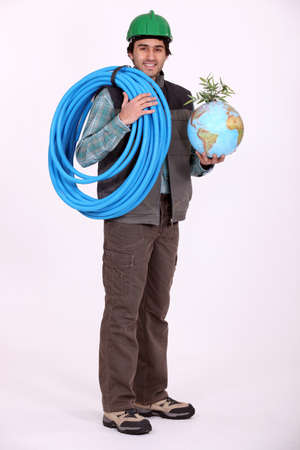 arose: craftsman holding a hose and a globe with a green plant on it Stock Photo