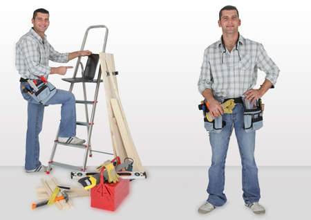 Happy woodworker with ladder, laptop computer and tools photo