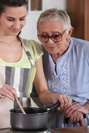 intergenerational: a senior woman looking a young woman cooking
