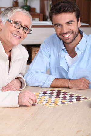 draughts: Mother and son playing draughts Stock Photo