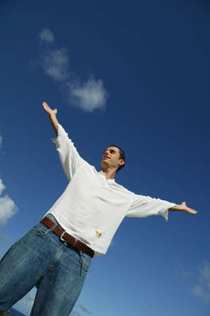 Man stood outdoors with his arms raised photo