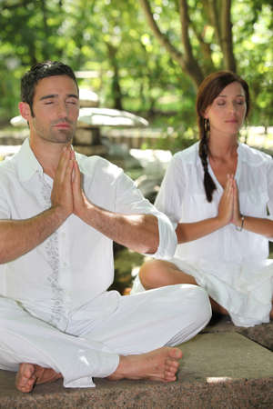 Couple meditating in stone garden photo