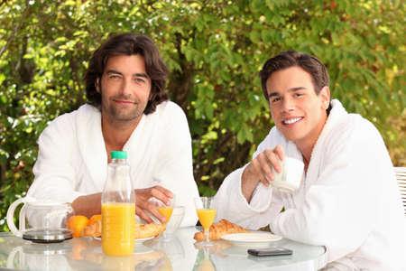 45 years old: 45 years old man and a 20 years old man dressed in bathrobe drinking coffee at breakfast Stock Photo