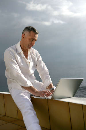 dismal: Man working on his laptop by the ocean