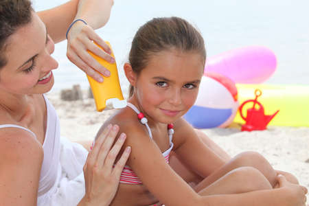 a mother putting sun cream on her daughter photo