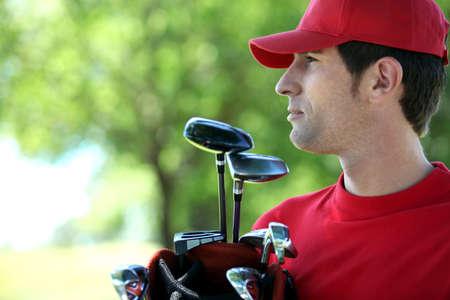 Golfer holding golf bag Stock Photo - 12302607