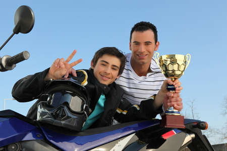 cornering: A young biker with a trophy.