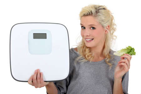 bathroom scale: blonde woman showing a bathroom scale and taking a lettuce leave