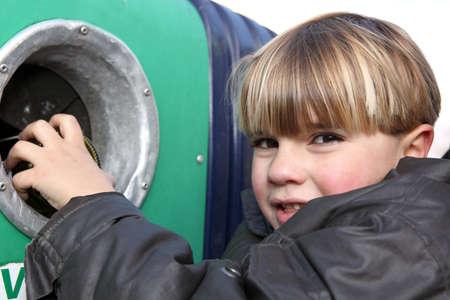 niños reciclando: El niño pequeño tirar una botella de cristal en un contenedor Foto de archivo
