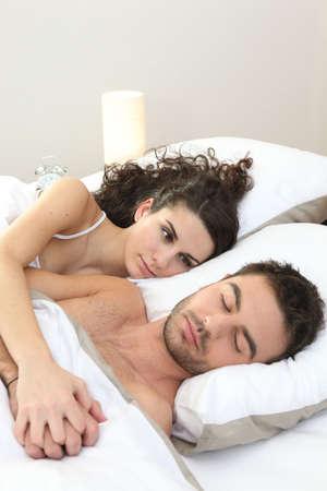 pareja durmiendo: una mujer contemplando su hombre durmiendo Foto de archivo