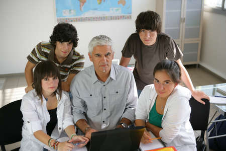 teacher with students: Pupils with their teacher and a laptop Stock Photo