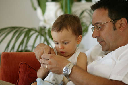Father sat on the sofa with toddler Stock Photo - 12302235