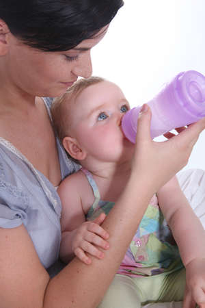 0 6 months: Girl giving baby her bottle