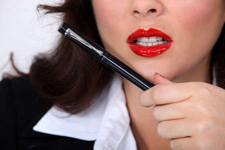 Closeup of a businesswoman with red lipstick holding a pen Stock Photo - 12302698