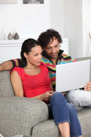 spare time: Couple looking at pictures on their laptop