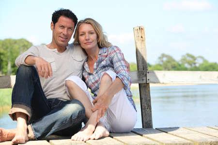 pontoon: mid age couple seated on a pontoon near a lake