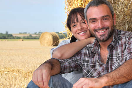 Farming couple sat by hay photo
