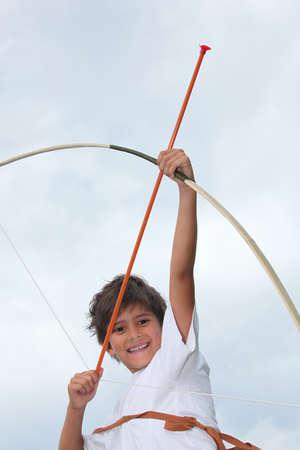 pull toy: Ni�o feliz jugando con arco y flecha Foto de archivo