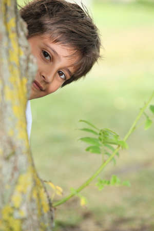 Young boy playing peek a boo around a tree photo