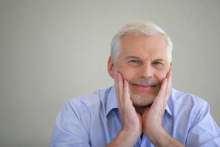 60 years old: Grey-haired man thinking back on his life Stock Photo