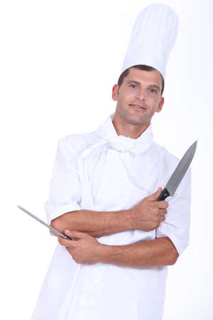 traceability: a butcher with a knife and a sharpener Stock Photo