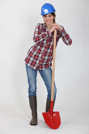 Tradeswoman leaning against a spade photo