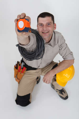 Man holding up a measuring tape photo