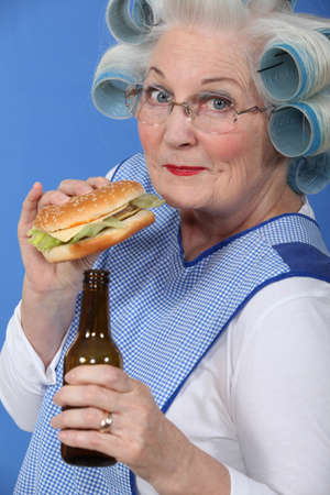Old woman in rollers with a burger and a beer photo