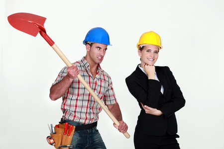 resentment: Construction worker preparing to hit an engineer over the head Stock Photo