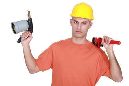 pressurized: Tradesman holding a pipe wrench and a blowtorch