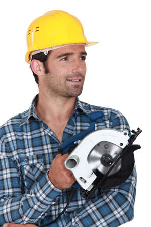 Carpenter stood holding circular saw photo