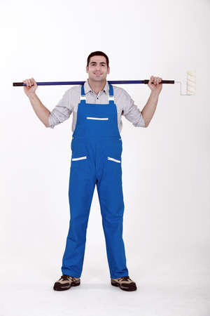 prime adult: Man stood with extended paint roller Stock Photo