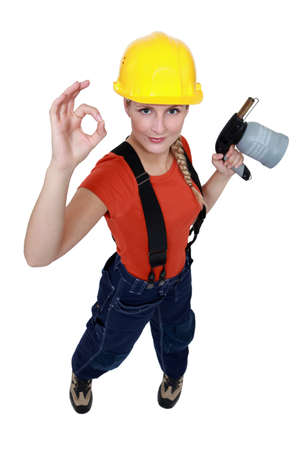 blowtorch: Tradeswoman holding a blowtorch and giving the a-ok sign Stock Photo