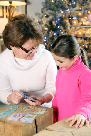 storytime: Grandmother and child playing cards at Christmas Stock Photo