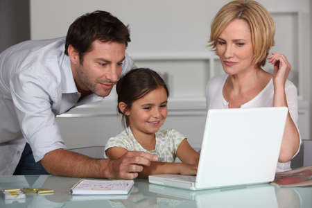 Young girl using a laptop computer with her parents photo