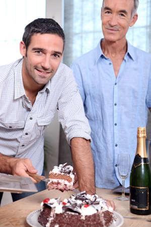 Two men cutting celebration cake photo