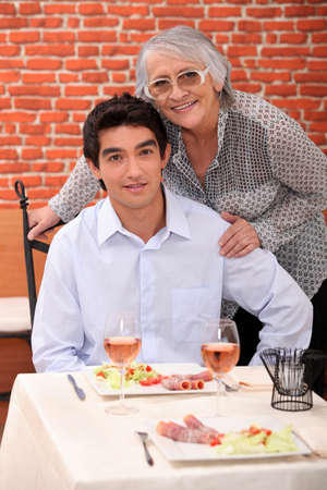 a young man and an old woman at the restaurant posing for the camera photo