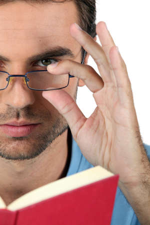 Closeup of a man in glasses reading a book photo