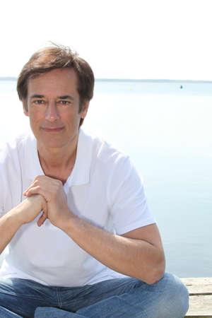 crosslegged: Man sat cross-legged on jetty