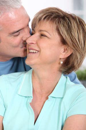 tenderly: Mature couple kissing tenderly Stock Photo
