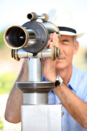 Middle-aged man looking through telescope photo