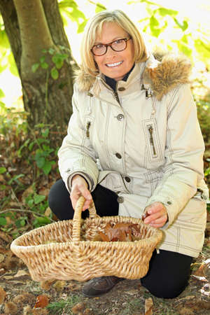 Woman gathering mushrooms in garden photo