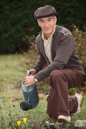 Man watering plants in his garden photo