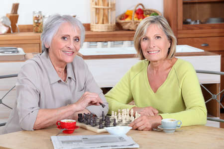 Two old women playing chess in kitchen photo