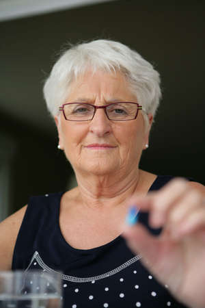 senior woman taking pills photo