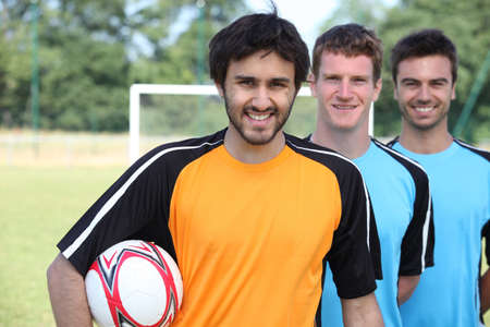 lineup: Three footballers in a line-up in front of goal Stock Photo
