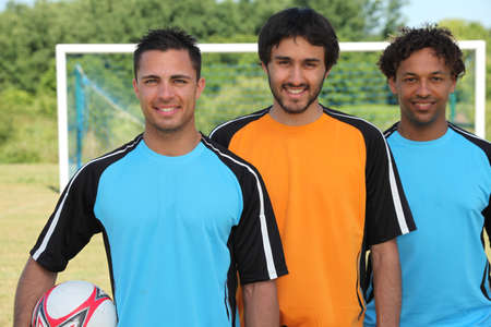 Three football players standing in front of goal Stock Photo - 12302494