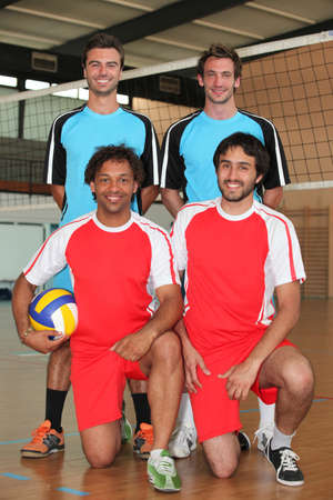 kneeling man: Two volleyball teams with ball on indoor court Stock Photo
