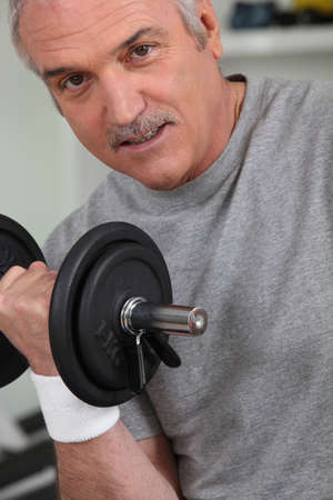 a mature man doing fitness with dumbbell photo
